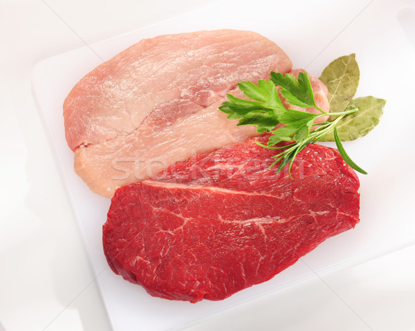 Raw pork chop and steak. Arrangement on a white cutting board. Stock photo © bogumil