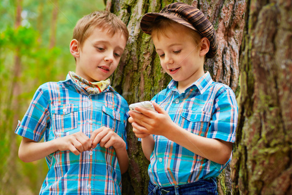 Young stylish boys browse the internet on mobile phone Stock photo © bogumil