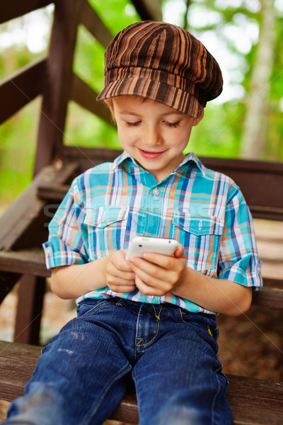 Young stylish kid playing games on mobile phone Stock photo © bogumil