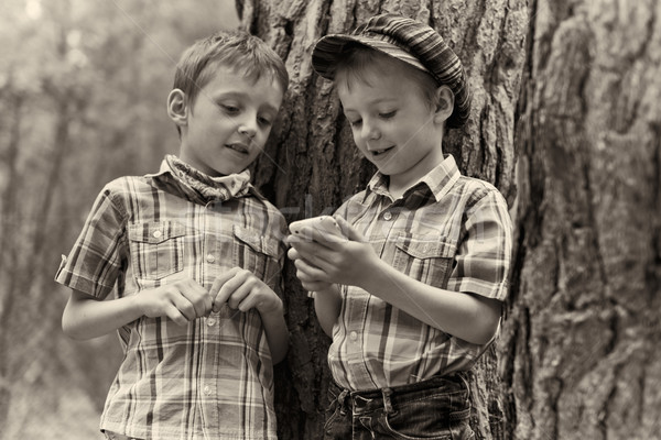 Young stylish boys browse the internet on mobile phone.  Stock photo © bogumil