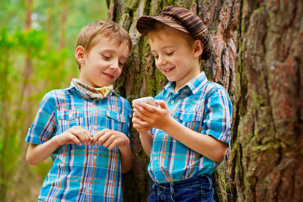 The kid is showing his brother various games on mobile phone Stock photo © bogumil