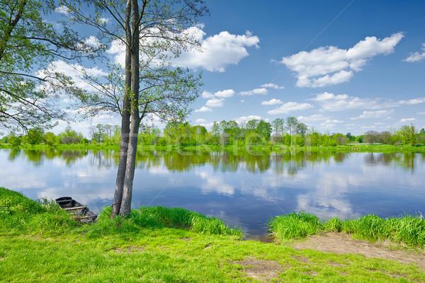 Rivier landschap oude boot rivieroever zonnige Stockfoto © bogumil