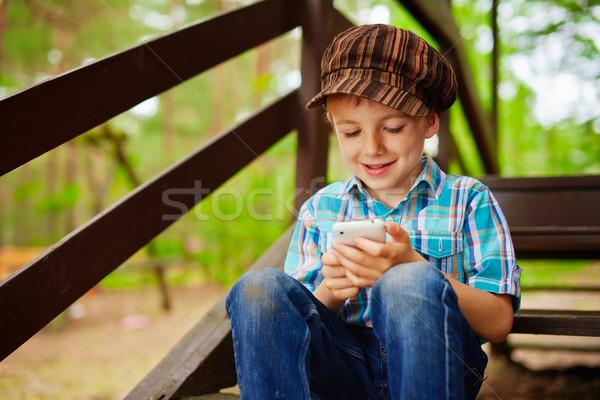 Young stylish boy browsing internet on mobile phone Stock photo © bogumil