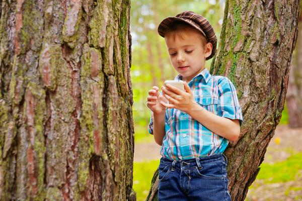 Fiatal elegáns gyerek olvas sms fiú Stock fotó © bogumil