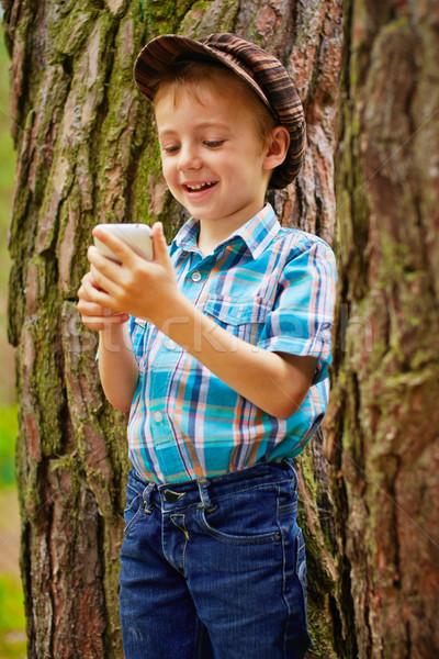 Téléphone jouer jeux arbre sourire Photo stock © bogumil