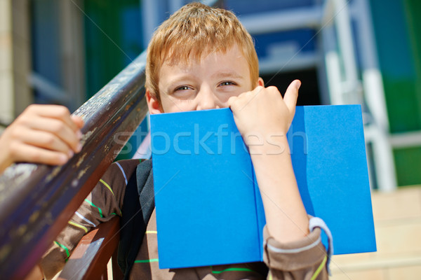Young boy is hiding behind book. Stock photo © bogumil