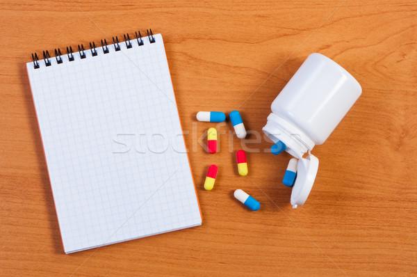 Notebpad and pills on table top view. Stock photo © borysshevchuk
