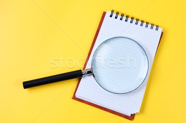 Magnifying glass and notepad on yellow background. Stock photo © borysshevchuk