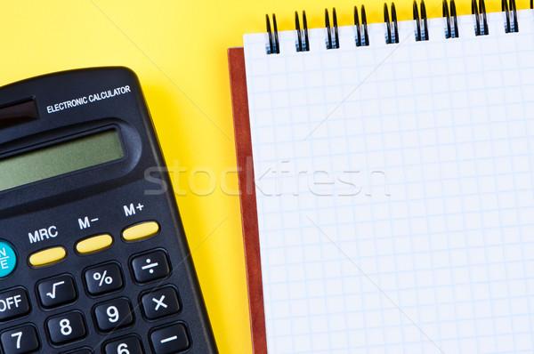 Notepad and calculator on yellow background. Stock photo © borysshevchuk