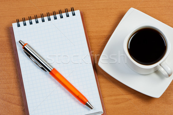 Notebook with pen and coffee on table top view. Stock photo © borysshevchuk