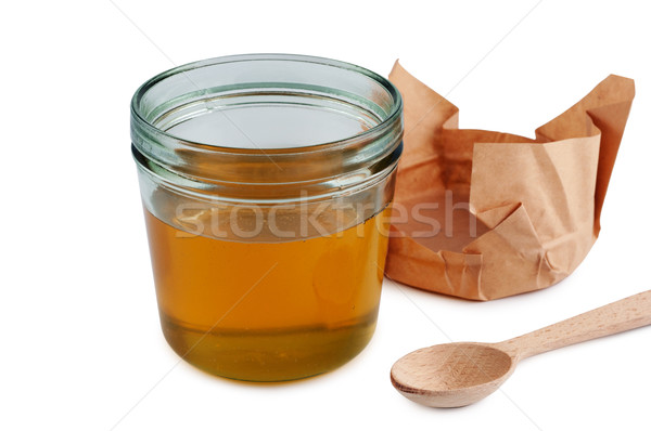 Honey in jar with wooden spoon. Close up isolated. Stock photo © borysshevchuk