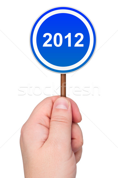 2012 road sign in hand isolated on white background. Stock photo © borysshevchuk