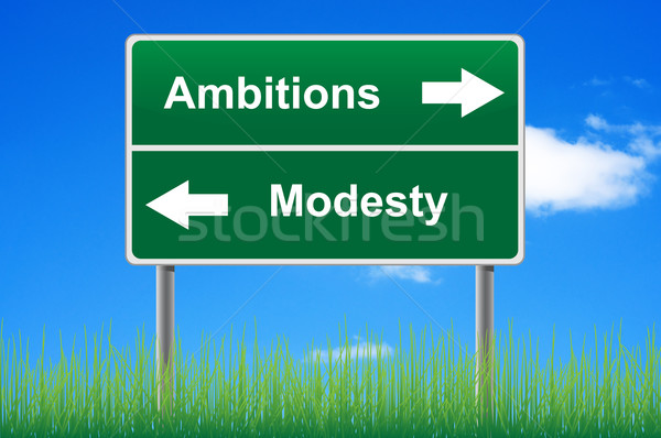 Ambitions modesty signpost on sky background, grass underneath. Stock photo © borysshevchuk