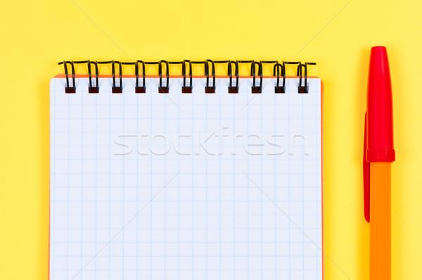 Notepad and ballpen on yellow background. Stock photo © borysshevchuk