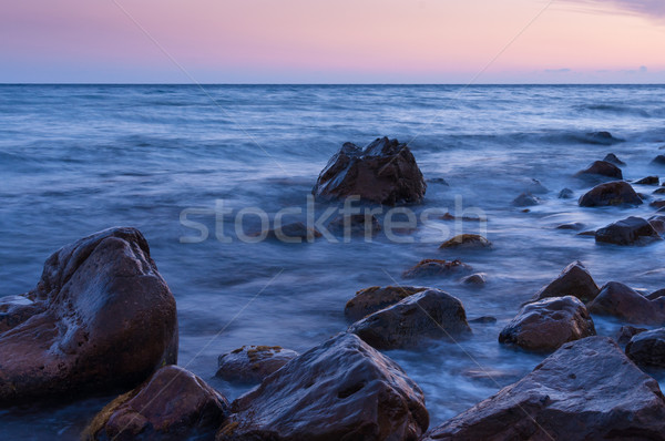 Sunset on sea. In foreground large boulders. Stock photo © borysshevchuk