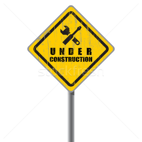 Stock photo: Old shabby road sign under construction.