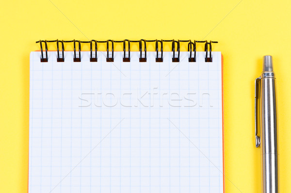 Notebook and ballpoint pen on yellow background. Stock photo © borysshevchuk