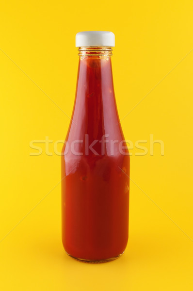 Ketchup in a bottle on yellow background. Stock photo © borysshevchuk