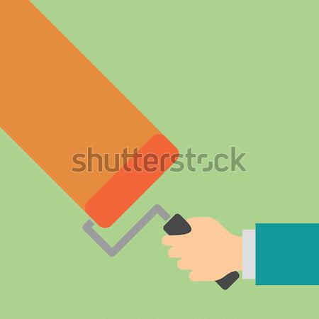 Hand with paint roller paints the wall. Stock photo © borysshevchuk