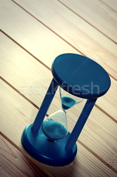 Hourglass on wooden surface. Stock photo © borysshevchuk