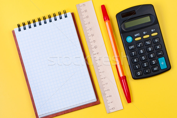 Calculator and notepad on yellow background top view. Stock photo © borysshevchuk