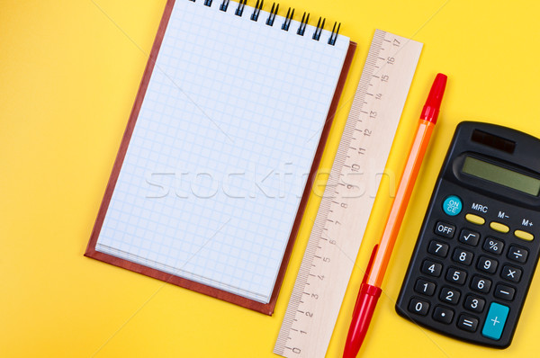 Pocketbook and calculator on yellow background. Stock photo © borysshevchuk