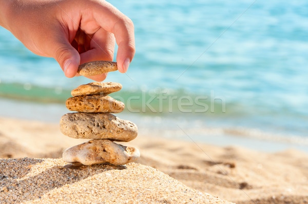 Stone tower on sand with hand against sea. Stock photo © borysshevchuk