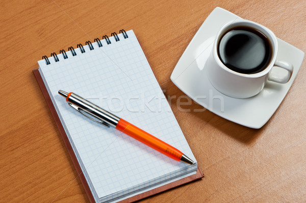 Notebook with pen and coffee on table. Stock photo © borysshevchuk