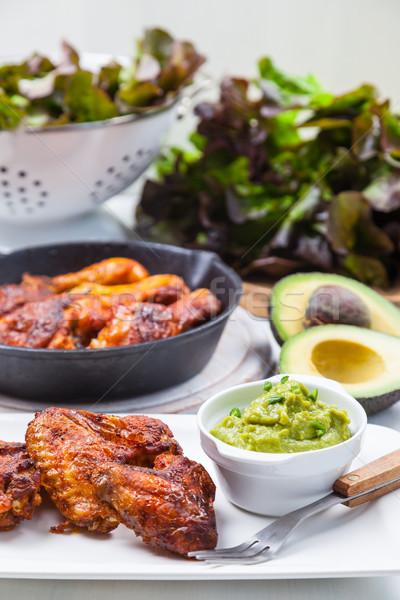 Grilled chicken legs and wings with guacamole Stock photo © brebca