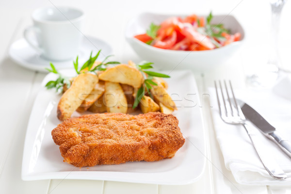 Schnitzel with wedges and tomato salad Stock photo © brebca