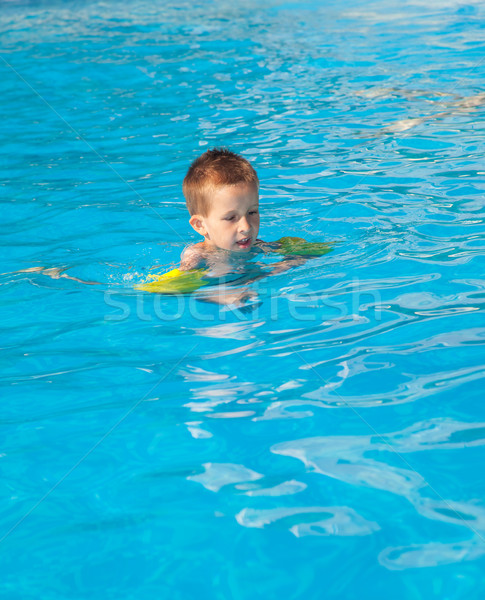 Happy boy swimming with floaties Stock photo © brebca