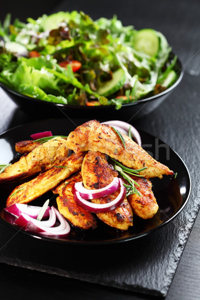 Marinated chicken breast stripes with salad Stock photo © brebca