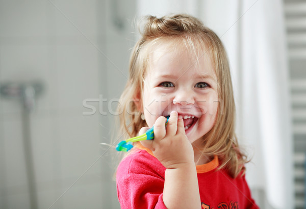Stock photo: Small girl washing her teeth