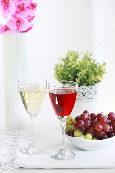 Stock photo: Two glasses of wine with grapes