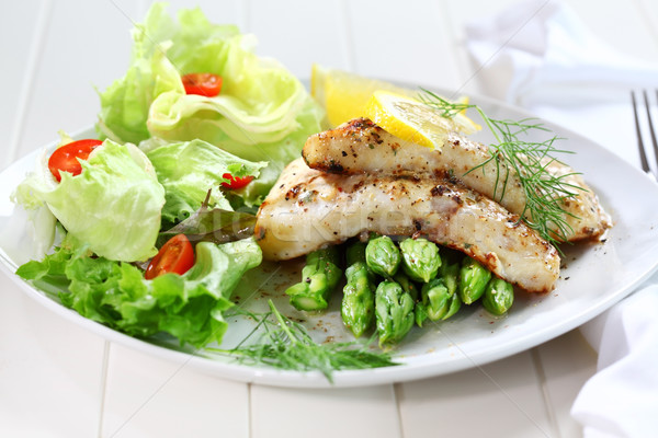 Fried fish on green asparagus with salad Stock photo © brebca