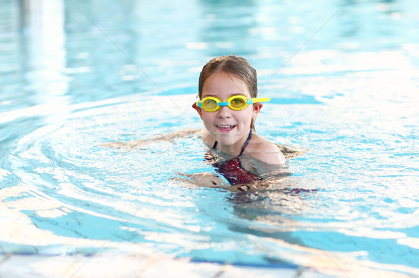 Schoolgirl with goggles in swimming pool Stock photo © brebca