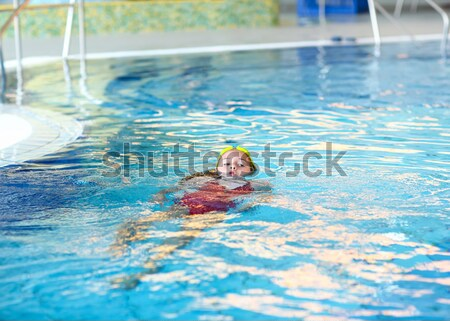 Happy girl with goggles in swimming pool Stock photo © brebca