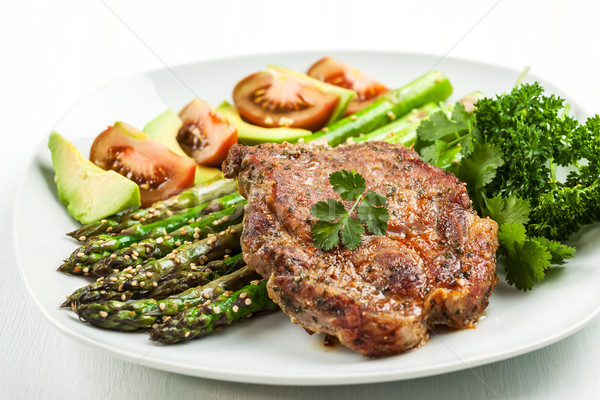 Glazed green asparagus with grilled pork chop Stock photo © brebca