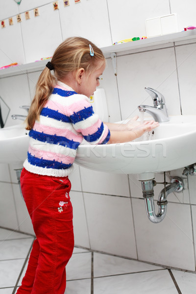 Small girl washing her hands in the bathroom Stock photo © brebca