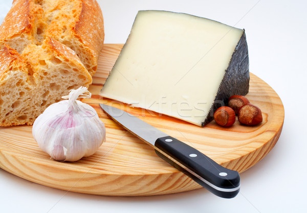 Stock photo: Cheese, bread, hazelnuts and knife on wood plate