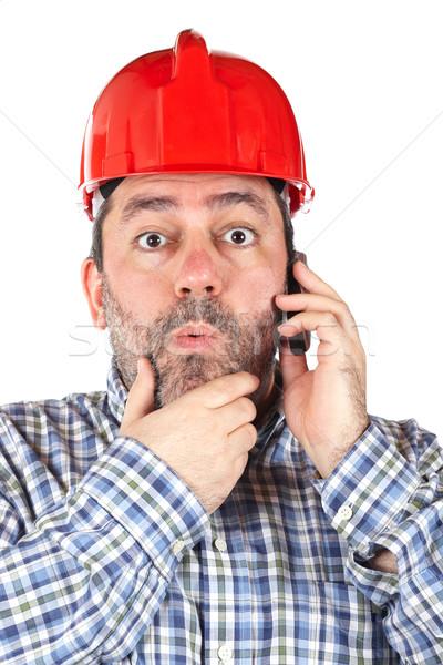 Sorprendido trabajador de la construcción casco de seguridad hablar teléfono aislado Foto stock © broker