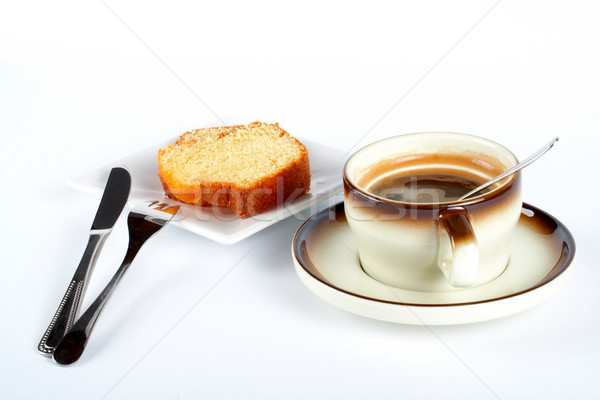 Sponge cake with the cup of coffee, spoon, knife and fork on white ceramic plate Stock photo © broker