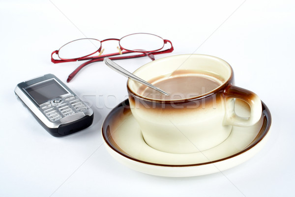 Close-up of a cup of coffee with the spoon inside, cellular phone and pair of glasses Stock photo © broker