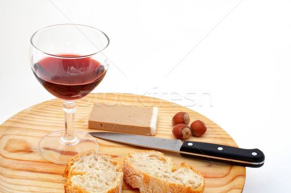 Pate, bread, glass of red wine, hazelnuts and knife on wood plat Stock photo © broker