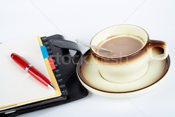 Close-up of a cup of coffee with the spoon inside and notebook with ballpoint Stock photo © broker
