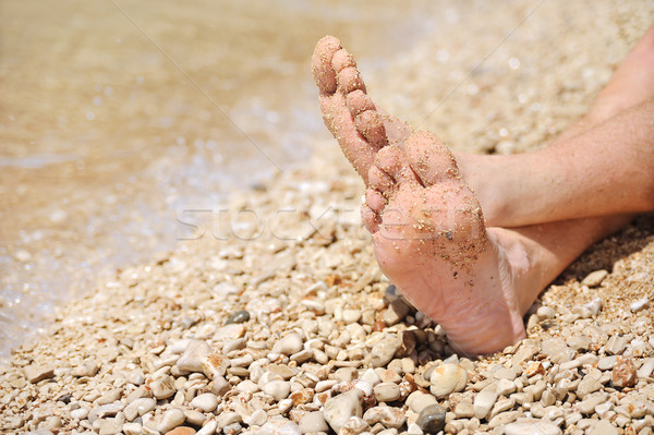 Relaxation on beach, detail of male feet Stock photo © brozova