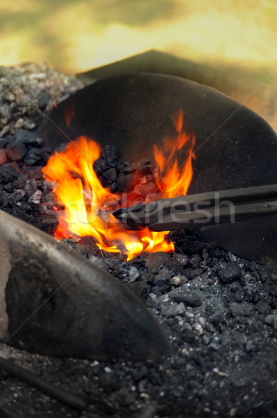 Blacksmith heating up iron - detail Stock photo © brozova