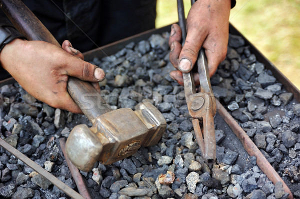 Stock photo: Detail of dirty hands holding hammer and pliers - blacksmith