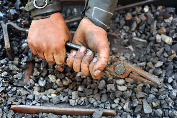 Stock photo: Detail of dirty hands holding pliers - blacksmith