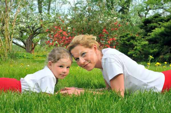 Stock photo: Young mother and daughter laying on the grass - practising